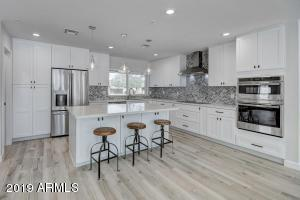 Updated & modern feel: The kitchen is perfect for entertaining! Stylish white cabinets, quartz counters island with seating, large pantry & new stainless appliances, lighting and fixtures!