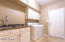 Large Laundry Room with Natural Stone Counter Tops and Sink