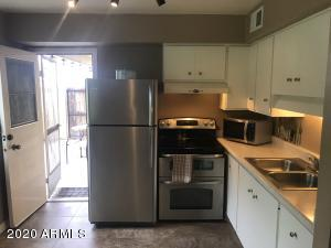 Kitchen has good lighting, stainless appliances, and is just off the patio