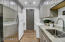 Laundry room, located behind the kitchen, with sink, built-in desk, and plenty of storage.