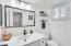 The second bathroom features bright lighting and white accents all throughout