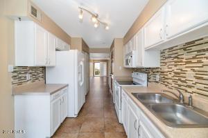 Light & bright kitchen features plenty of cabinets, white appliances & glass mosaic backsplash!