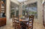 Spacious casual dining area next to the kitchen overlooks the backyard and boasts custom alder shades for maximizing the view.