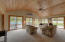 Sunroom is carpeted with wood planked vaulted ceiling and ceiling fan.