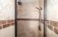 Walk-in custom tile shower with rain head.