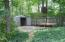 Corner of backyard with large concrete slab, basketball goal and lawn storage shed.