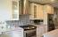 Kitchen has a new modern and sleek design with Stainless Appliances, Mosaic Tile Back-splash, Glass canopy mounted Hood, and a Farmhouse Stainless Kitchen Sink