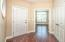 Engineered hardwood flooring, tan painted walls, can lighting, round window, coat closet with french doors.