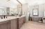 Master bath with expansive double sink quartz counter and custom cabinetry