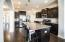 Beautiful kitchen with espresso cabinetry. Sellers upgraded the pendant lighting (stainless steel) Large island! Lower cabinets have pull-out drawers.