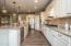 • New laminate flooring ~2017 • Mindful grey painted walls • Granite countertops • White cabinets • Tumbled marble backsplash • Pendant lighting • Center island with breakfast bar ledge • Kitchen Aid® refrigerator • Whirlpool® dishwasher • Whirlpool® microwave/oven combination • Range hood • Kitchen Aid® gas range • Step in pantry closet • Can lighting