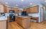 Eat-in Kitchen (20'5 x 11'5) features hardwood flooring, ample cabinets & counter space, center island, black appliances, recessed & designer lighting, pantry closet, door to Sunroom, and hall to Half Bath, Mud Room, and Laundry