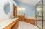 Owner's Bath features tile flooring, (2) vanities, whirlpool tub, glass enclosed shower, private water closet, walk-in closet, vaulted ceiling, and designer lighting