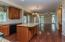 Eat-in Kitchen (20'4 x 15') features hardwood flooring, granite counters, center island with breakfast bar, black appliances, built-in planning desk, recessed & designer lighting, and door to rear deck