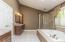 Owner's Bath features his & hers vanities with granite counters, whirlpool tub, glass enclosed shower, medicine cabinets, and private water closet