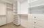 Custom owner's walk-in closet with shelving, shoe cubbies, drawers and more!