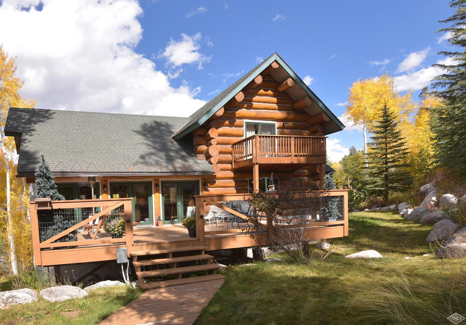 This custom-built log home surrounded by wildlife and national forest is the perfect place to relax and unwind. The main floor is perfect for entertaining or cozy nights by the fire - high vaulted ceilings provide a spacious feel in the living room which leads out to the back porch and hot tub overlooking National Forest. A massive wok provides ample opportunity to chef up in this kitchen. Downstairs, two bedrooms share an additional living and dining area and an exercise room leads into an in-law suite equipped with a separate kitchen, dining room & washer/dryer. Upstairs, the master and guest room enjoy private decks with gorgeous views. Plenty of room for ten people to sleep comfortably. The craftsmanship and detailing in this home is not to be missed. No words can describe the serenity while sitting on the back porch of this home - come see for yourself.