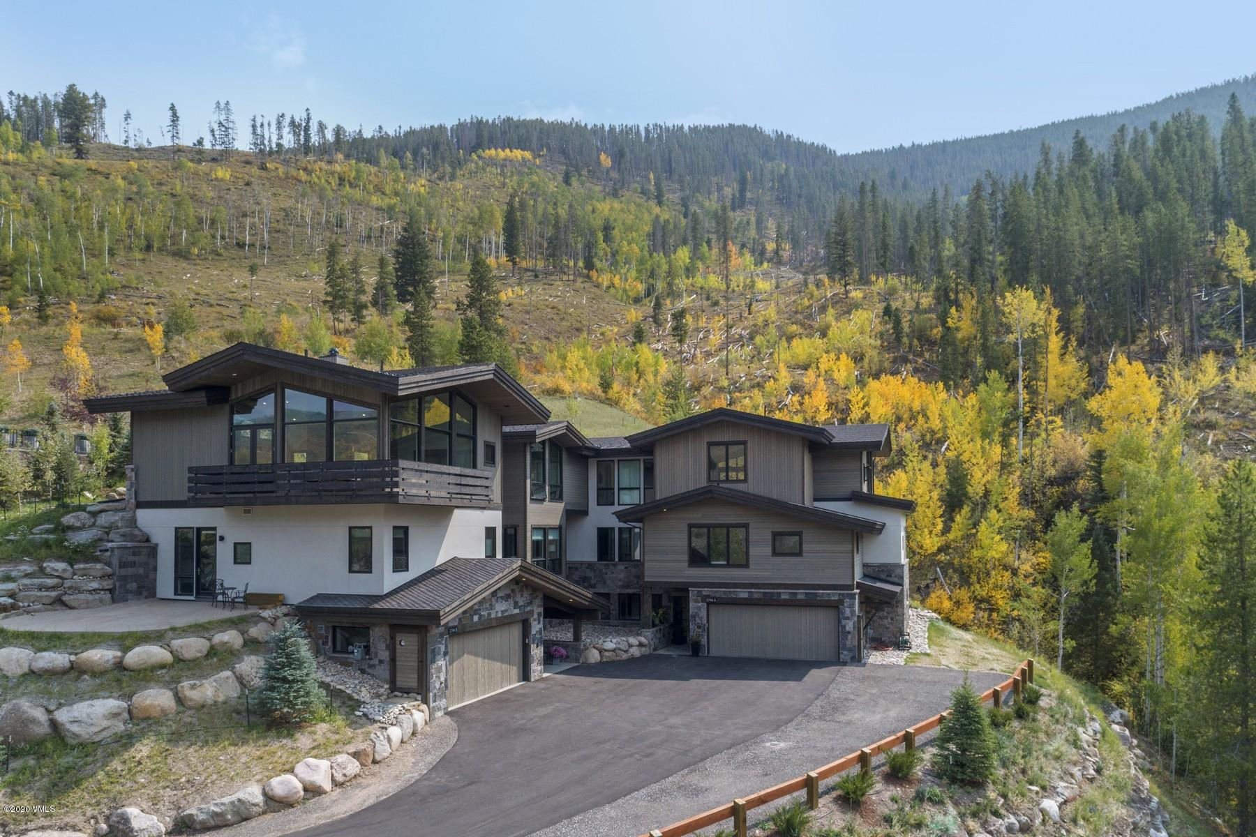 This spectacular new construction home is a harmonious blend of innovation and design. Situated at the top of Intermountain in West Vail, the 4-bedroom, 5-bath home is adjacent to open space with an abundance of magnificent views.The delightful layout on the main level encourages easy entertaining or cozy nights centered around the three-sided DaVinci fireplace. A second family area is found one floor below. The heated patio ensures year-round enjoyment.A gourmet kitchen is teeming with hidden surprises throughout. The statement piece and gathering place is the palatial island featuring a black-stained rift cut white oak base with contrasting Misterio Pental Quartz polished countertops. Relish every moment of the cooking process using the functional, yet beautiful Wolf appliances which include the 36-inch range, double ovens, steam oven, built-in coffee system, Sub-Zero refrigerator and microwave drawer. Custom hard maple cabinetry from Cutting Edge Woodworking seamlessly conceals the refrigerator and dishwasher as well as extras like the built-in spice drawer, knife holders and waste receptacles. Clean-up is also a breeze with the Asko dishwasher. Fulfilling the idea of seamless transitions throughout the home is the Sonos Surround Sound system with speakers in the great room, master suite, kitchen, and outdoor living spaces.  The home also features a commercial elevator, is pre-wired for a security system, has in-floor radiant heat throughout and features an Energy Recovery Ventilation (ERV) system that brings clean, fresh air into the home while maintaining the inside temperature. mls.snowberryluxury.com