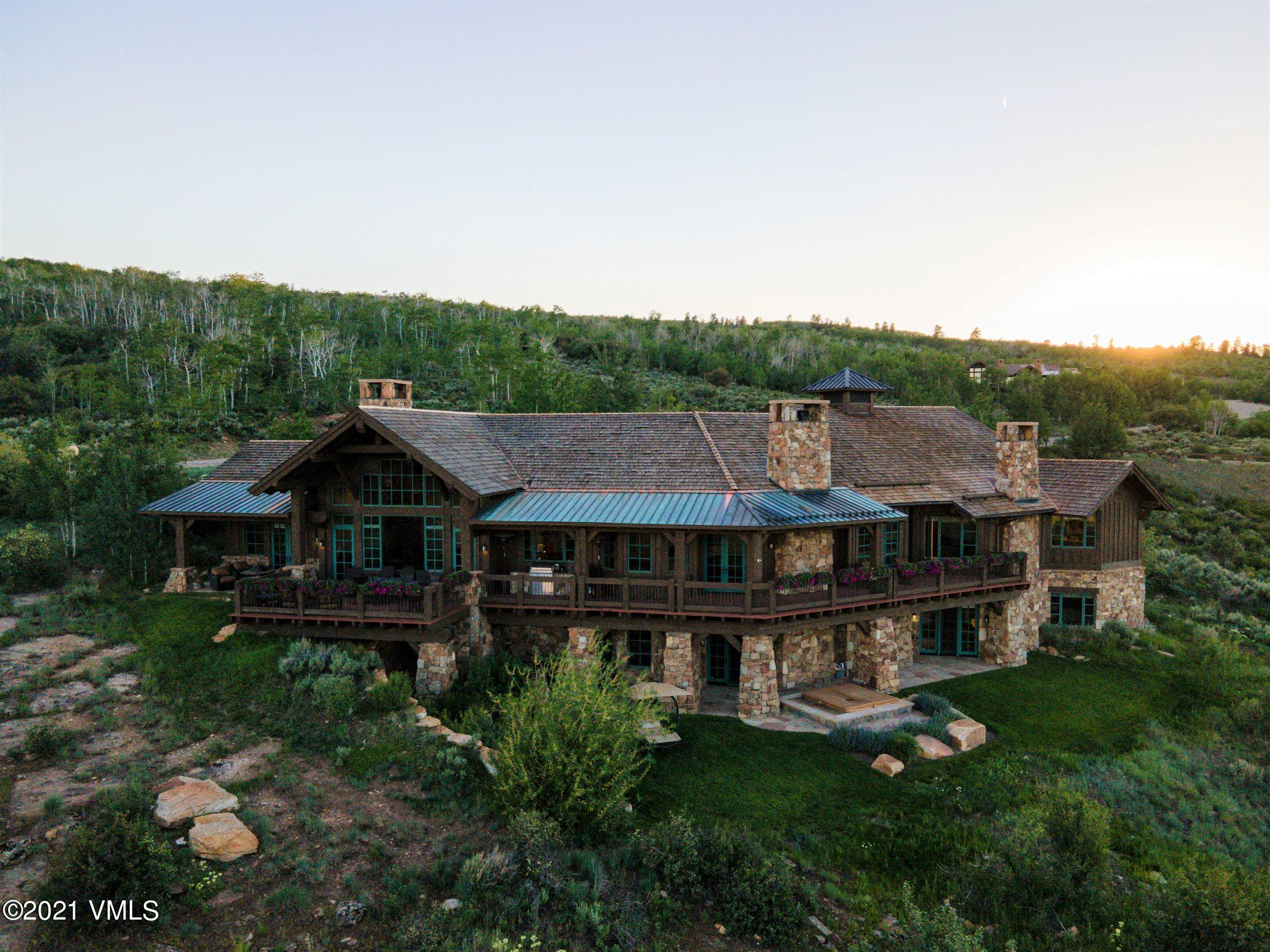 Presenting 50 Eagle Feather, Red Sky Ranch!  Here is a unique opportunity for you to own a stunning ranch - style mountain home in the renowned golf community of Red Sky Ranch. 50 Eagle Feather sits on just over 2 acres adjacent to the 13th tee box in a very private, serene location offering views of the Gore Range, Vail's back bowls and the Red and White Mountains. The expansive covered deck spans the entire length of the home and draws you and your guests out to engage with the surrounding natural landscape of fragrant sage, wildflowers and natural rock formations.  The home exudes warmth with its massive ceiling beams and sandstone lintels, complimenting the open floorplan that flows seamlessly from the kitchen and hearth room to the dining and living rooms to create plenty of comfortable entertaining spaces. Open the multiple French doors leading from the dining room to view the sunset from the front porch patios while surrounded by aspen trees and gorgeous beds of native Columbine flowers.The main level encompasses a private, spacious primary bedroom suite with large his and hers closets, fireplace, granite-topped make-up area, soaking tub and stone shower.  A lovely secondary suite with fireplace awaits the fortunate guests. The lower level features a stunning stone wall and arches leading to two secondary bedroom suites, a family room with big screen tv and game tables for gathering.  The kitchen/bar area includes a temperature controlled 600+ bottle wine room, and the walk-out stone patio features a hot tub spa. The upper decks include a Niles sound system with 5 zones, and a built-in outdoor grill connected to natural gas supply. Other amenities include 4 fireplaces, a 3-car garage with 220V outlet in garage for electric car charging, and extensive, mature landscaping, Welcome home!