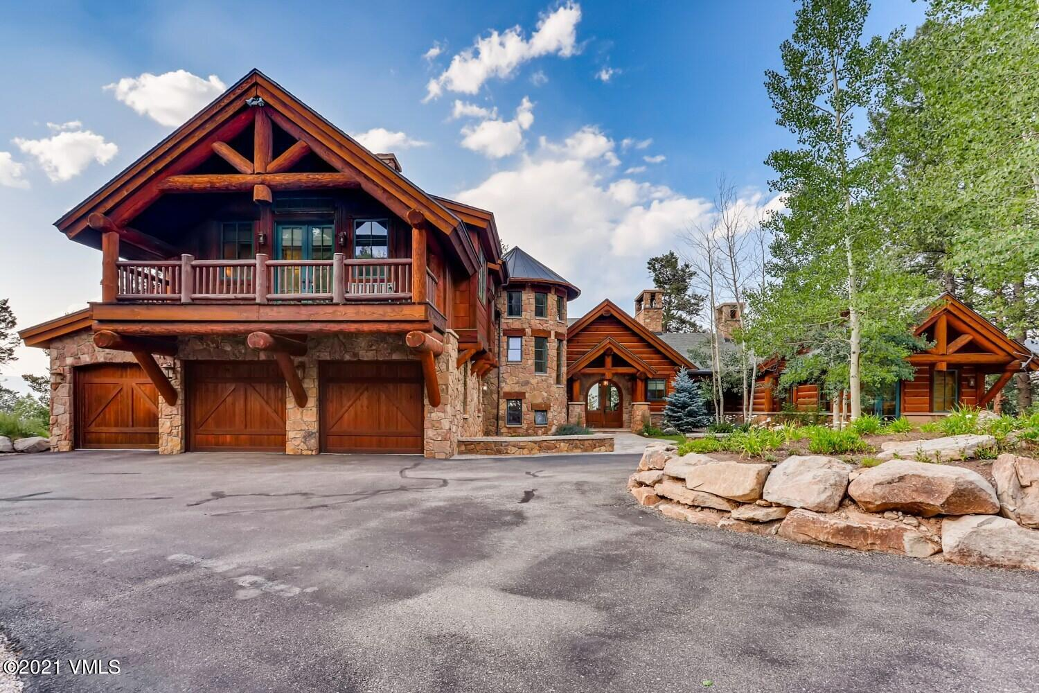 Located in the exclusive gated community of Travis Creek, this beautifully designed custom log home features 7907 sqft, 5 bedrooms, large beams, vaulted ceilings, & high-end finishes. This fine home, designed with an open floor plan perfect for entertaining, includes hearth/kitchen/dining combo, large great room, main level primary, & exercise room. The main level exterior includes a wrap-around deck, covered grill with dining, & covered TV area. The upper level includes a guest suite with sitting area & wet bar. The lower level has 3 bedrooms (and a bunk room), wet bar, family room, home theater, & wine cellar with dumb waiter to kitchen. Ground level exterior features a flagstone patio, recessed hot tub, water feature, fireplace, children's play cabin with bunks, fire pit, & separate deck. Wired for sound & security system. HOA dues include security gate, snow removal, & trash collection. Nearby Red Sky Golf Club boasts 2 ranked golf courses, clubhouse dining, tennis, & swimming. Property is being sold furnished with the exception of the artwork, personal items,  personal accessories, and select exclusions. The Sellers shall provide a list of exclusions which will accompany this listing. Sellers also are in the process of replacing the following appliances: refrigerator in kitchen, warming drawer in kitchen, and ice maker in downstairs family room.