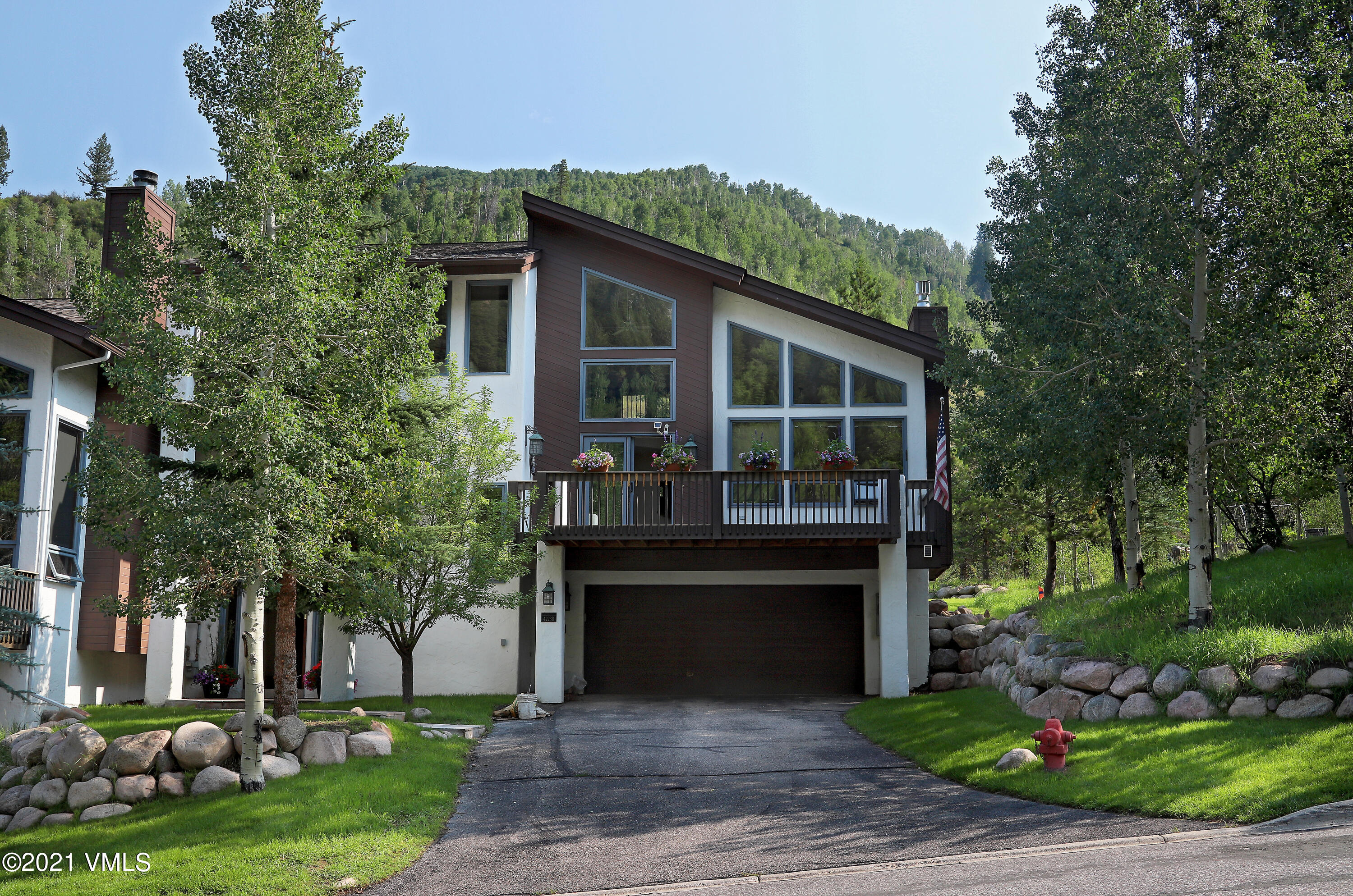 With beautiful mountain views, large decks, a flat, grassy back yard and separate driveway, the primary side of this duplex lives like a single-family. The home's towering ceilings and large windows welcome in morning sun while the mature aspens and evergreens that surround it provide afternoon shade on a quiet, picturesque street in East Vail. The open concept main floor has a spacious living room with modern gas fireplace encased in a beautiful, stacked stone chimney, abundant natural light, dining area, and walk-out access to both front and back decks. The large kitchen has Tuscan-inspired tile backsplash, slab granite countertops, and stainless steel appliances including 6-burner Wolf gas range and oven. Two large bedrooms each with their own bath complete the main floor. The upper level features a large master suite with walk-out deck and 2 adjacent bonus spaces for a home office, library, greenhouse, hot tub, sauna, play room, yoga area, art studio or whatever you need! The focal point of the updated 5-piece bath is its classy, entrend, free-standing tub. The lower level has a creatively designed space that is currently doubling as a separate family room and 4th bedroom with tastefully updated 3/4 bath. Finally, you won't believe the built-in storage and work spaces in the oversized 2-car garage complete with wash sink and extra freezer. Don't miss this incredibly spacious home with 3 total decks, a great yard for the dog or kids, plenty of parking for you and your guests, and easy access to I-70.