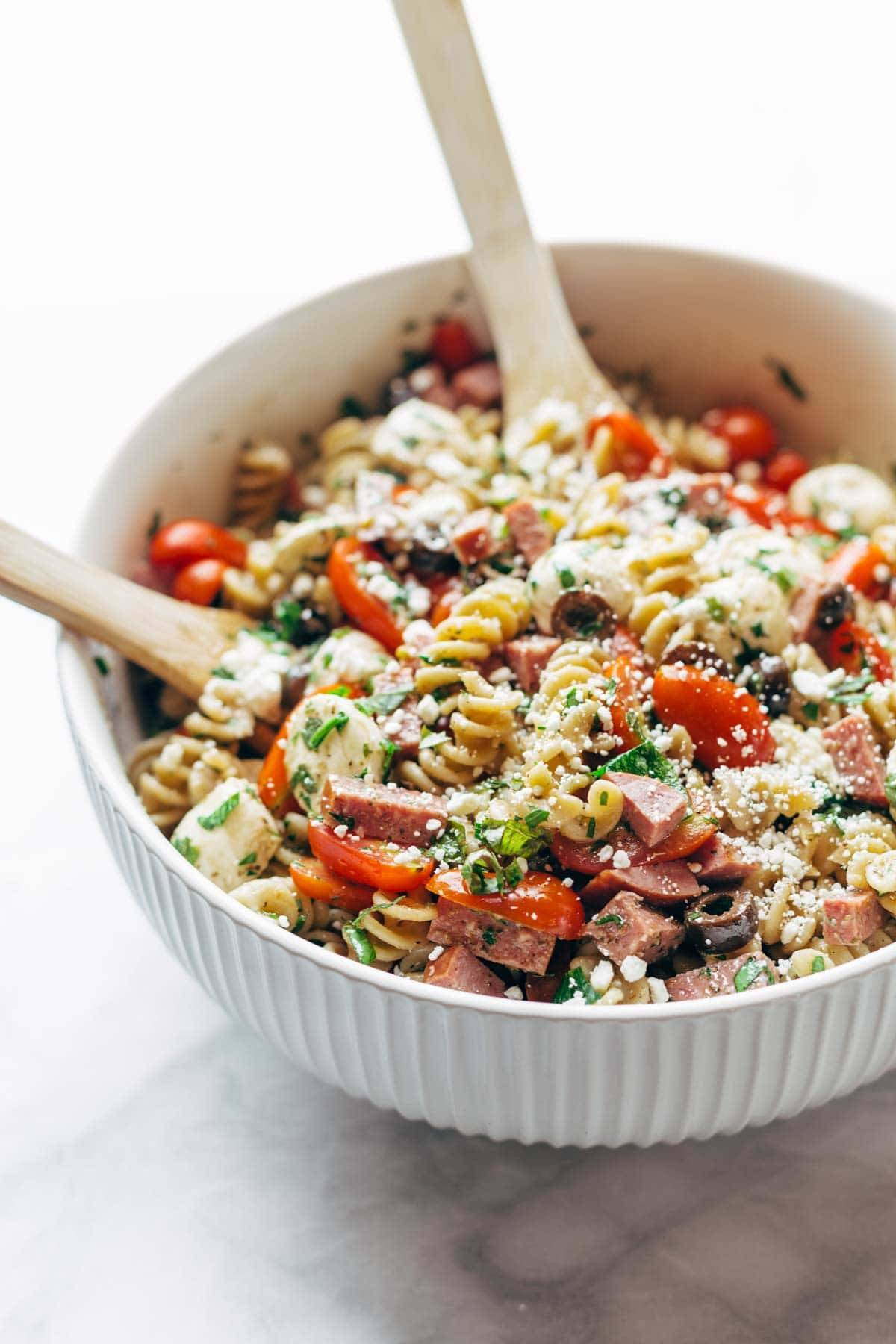 Best Easy Italian Pasta Salad - with pasta, tomatoes, fresh mozzarella, spicy salami, parsley, olives, and easy Italian dressing. Super versatile to what you have on hand! | pinchofyum.comc