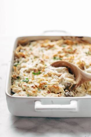 Chicken Tetrazzini in a pan with a wooden spoon.
