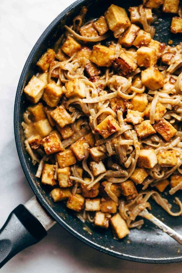 Fried tofu and brown rice noodles with sauce in pan.