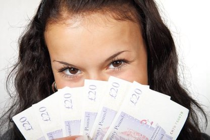 A woman's face partially hidden by a wad of bills she is displaying