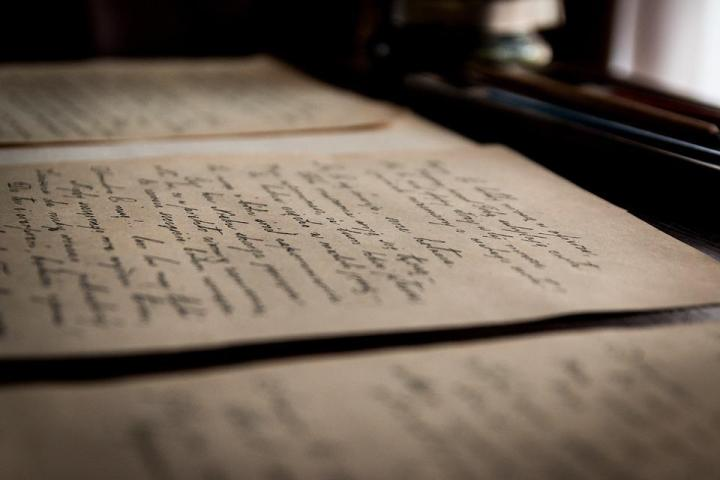 Sheets of hand-written text lit by soft light through curtains.