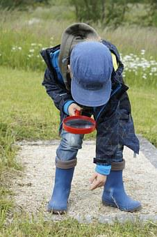 A boy looking at something on the ground through a magnifying glass
