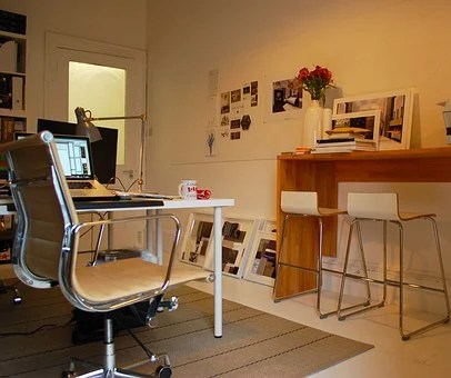 A home office showing a desk, chair, laptop and other office equipment
