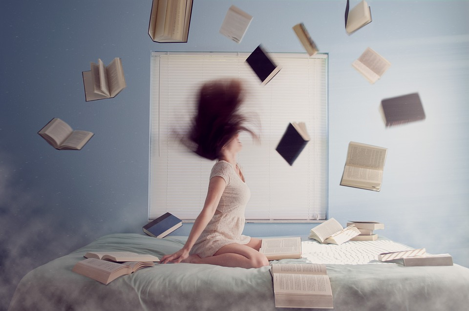 girl with long hair on bed with magic books open flying around her