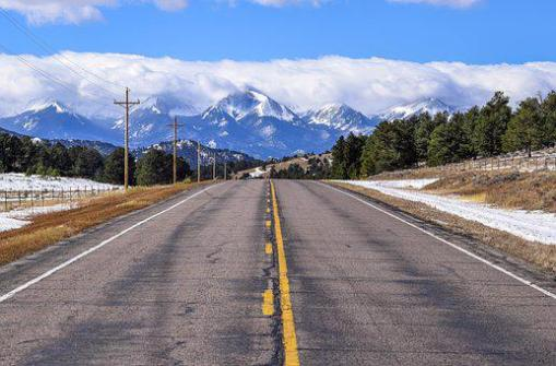 Mountain road in Colorado leading into snow capped mountains