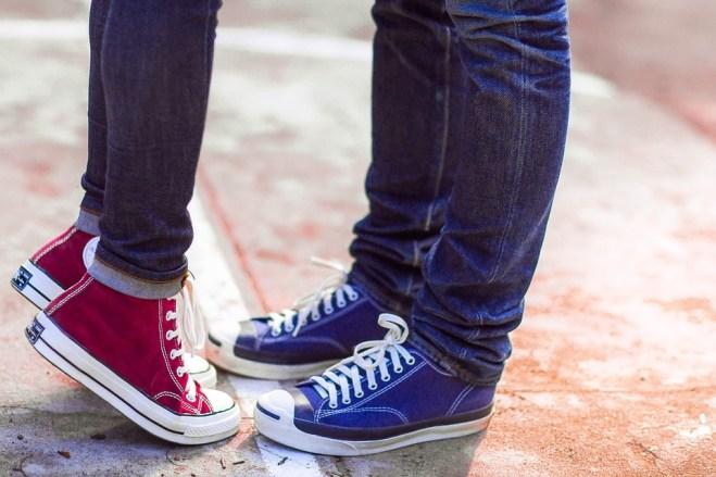 I piedi di una coppia, sono uno di fronte l'altra. Lei è in punta dei piedi ed indossa delle All Star bordeaux, lui le ha blu, entrambi indossano dei jeans