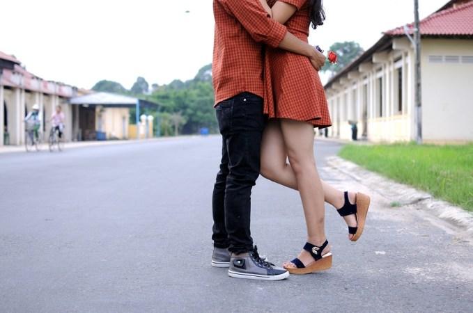 sul bordo della strada una coppia si abbraccia, lui indossa una camicia, jeans neri e snikers grigie. Lei indossa un abito corto e dei sandali neri di sughero. Il tessuto della camicia di lui e di lei è uguale a quadretti arancio e ruggine.