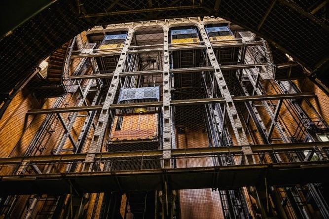 La vista del hueco de ascesores de un edificio con un ascensor circulando y tres más parados en la última planta visible en la imagen.  https://pixabay.com/es/photos/ascensor-levante-elevador-de-carga-5001019/  por https://pixabay.com/es/users/tama66-1032521/