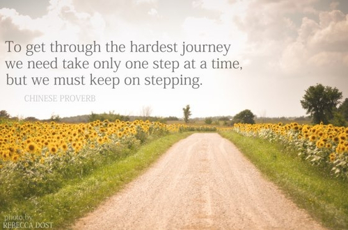 "A dirt road separating an open field of sunflowers. The text reads ""To get through the hardest journey we need take only one step at a time, but we must keep on stepping"" attributed to a Chinese proverb. Photo by Rebecca Dost."