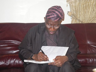 President Jonathan signs the condolence register at the Abatis home