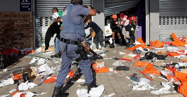A policeman tries to control looting by Zuma rioters