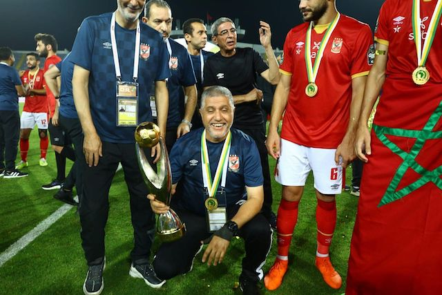 Al Ahly officials pose with the Total CAF Champions League trophy