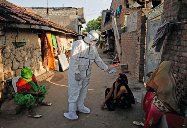 Testing people's temperatures in the state of Gujarat: More than 1,000 people are dying every day.