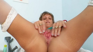 Skinny cougar gray nurse toys her piss hole on gynochair Preview Image