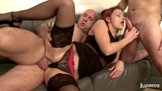 Red headed bitch in black stockings rides two massive dicks Preview Image
