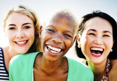 Three women smile together warmly