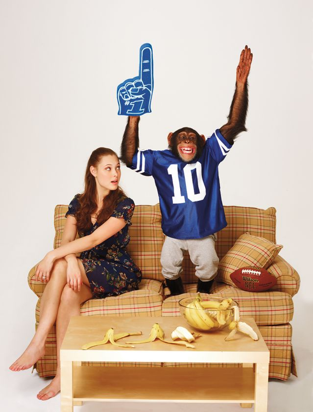 Chimp cheering for sports on a couch w/ human spouse watching