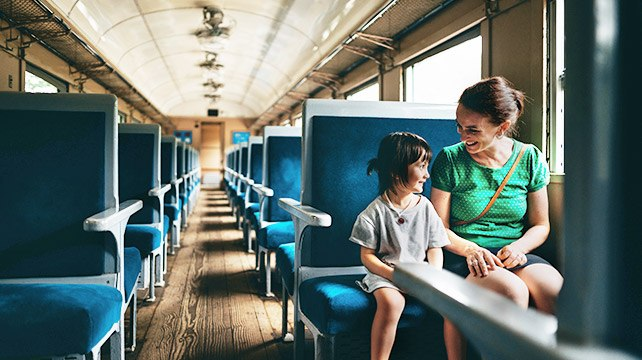mother and child traveling on empty train