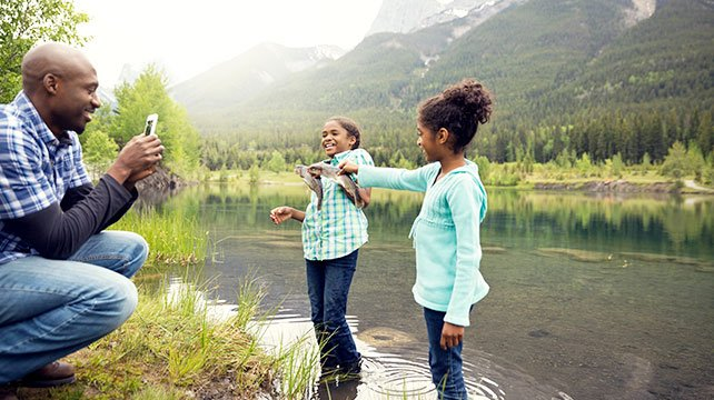 dad taking picture of daughters holding fish by a lake and smiling
