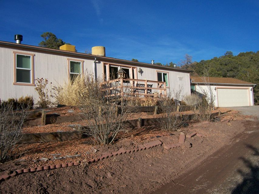 CASH Purchase Only * Super Opportunity to Own a Secluded Property Nestled Within the Pine Trees of Tijeras! With Nearly 3-Acres of Land, This 1896/Sq.Ft., Home Offers 3-Bedrooms, 2-Full Bathrooms, 2-Living Areas w/Center 2-Way Wood-Burning Fireplace, and Open Kitchen w/Separate Dining Space * Large Master Bedroom w/Spacious Closet & Master Bath Providing Separate Shower, Garden Tub and Double-Sinks * 2-Car Garage w/Attached 300/Sq.Ft. Office/Shop...or Could be Separate Guest Quarters * Lien-Holder is firm with List Price * Home needs work * Call a Broker and Visit Today!