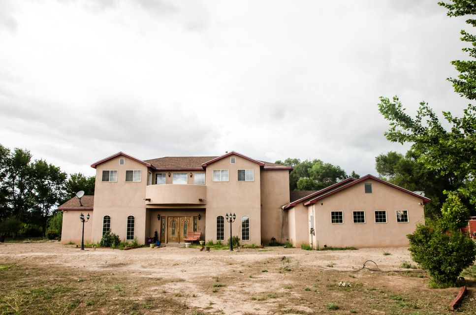 Enter a tree-lined lane to this Beautiful Custom Country Home located on 2.2 acres in Los Lunas.  The Open Living and Kitchen Area are Great for Entertaining with French Doors opening up to green grass and a tree filled backyard.  The huge gourmet kitchen is complete with stainless steel appliances, a walk in pantry and other quality finishes.  The land is surrounded with numerous trees & cottonwoods. This wonderful location is only 20 minutes to Albuquerque, you will appreciate the convenience!